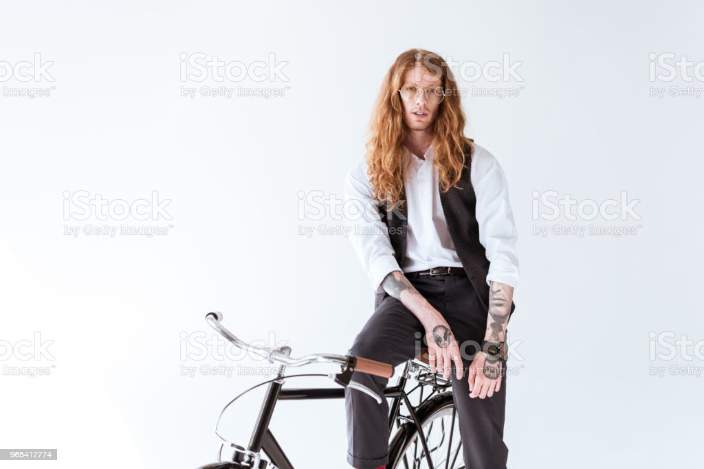 stylish tattooed businessman with long ginger hair sitting on bicycle isolated on white royalty-free stock photo