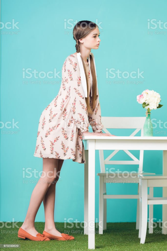 elegante menina adolescente com tranças em pé na mesa com buquê de flores, em turquesa - foto de acervo