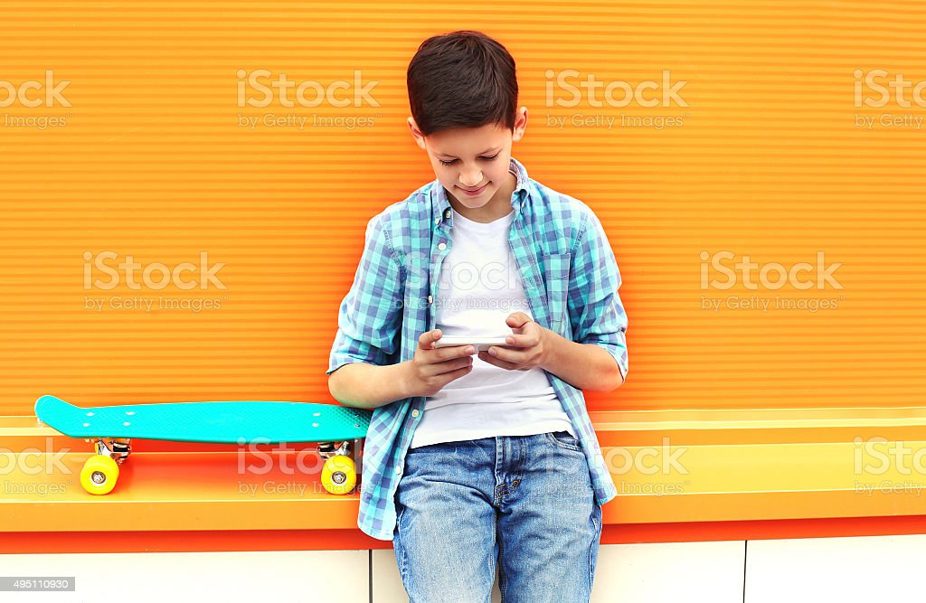 Stylish teenager boy with skateboard using smartphone in city ov stock photo