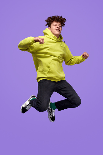 Full body happy youngster in trendy outfit looking at camera and jumping high against vivid purple background