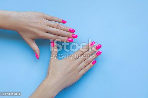 istock Stylish trendy female manicure. Beautiful neon plastick pink nails on blue background. 1170051014