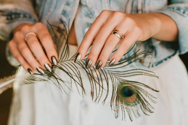 Stilvolle trendige weibliche Spiegel Maniküre, Metall Nagelkunst, halten Pfau Feder – Foto