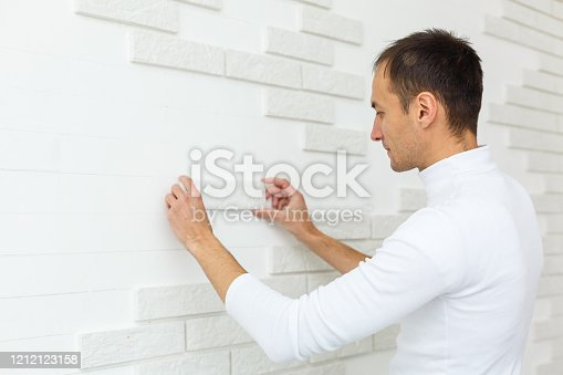 istock Stylish trendy white ceramic tile with a chamfer on the kitchen wall. Tiler hands in the process of laying white rectangular tiles on bathroom wall. Repair of apartments and bathrooms. 1212123158