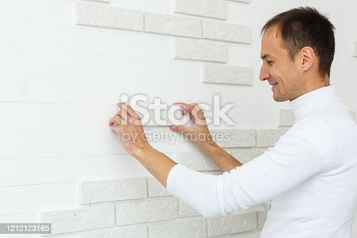 istock Stylish trendy white ceramic tile with a chamfer on the kitchen wall. Tiler hands in the process of laying white rectangular tiles on bathroom wall. Repair of apartments and bathrooms. 1212123165