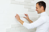 Stylish trendy white ceramic tile with a chamfer on the kitchen wall. Tiler hands in the process of laying white rectangular tiles on bathroom wall. Repair of apartments and bathrooms.
