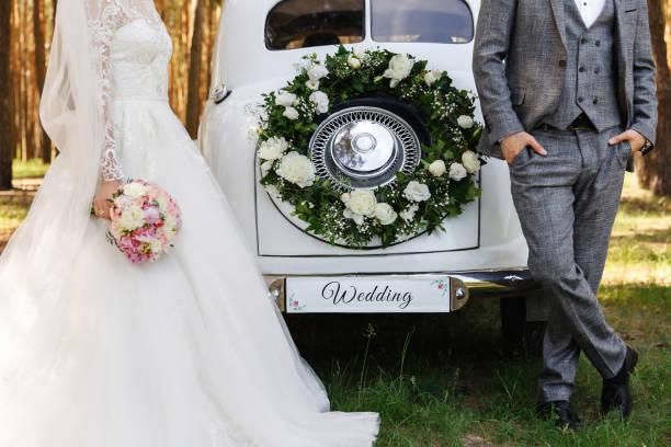 Stylish wedding couple, elegant newlyweds, groom and bride posing near white Just Married car with inscription ''Wedding'' stock photo