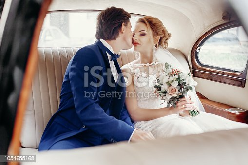 stylish wedding couple sitting inside of luxury car on white leather, embracing and kissing. elegant groom and bride romantic moments, wedding day concept