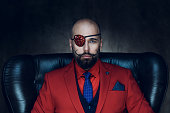 Portrait of handsome man wearing red jacket on dark background. Styled, well dressed man.