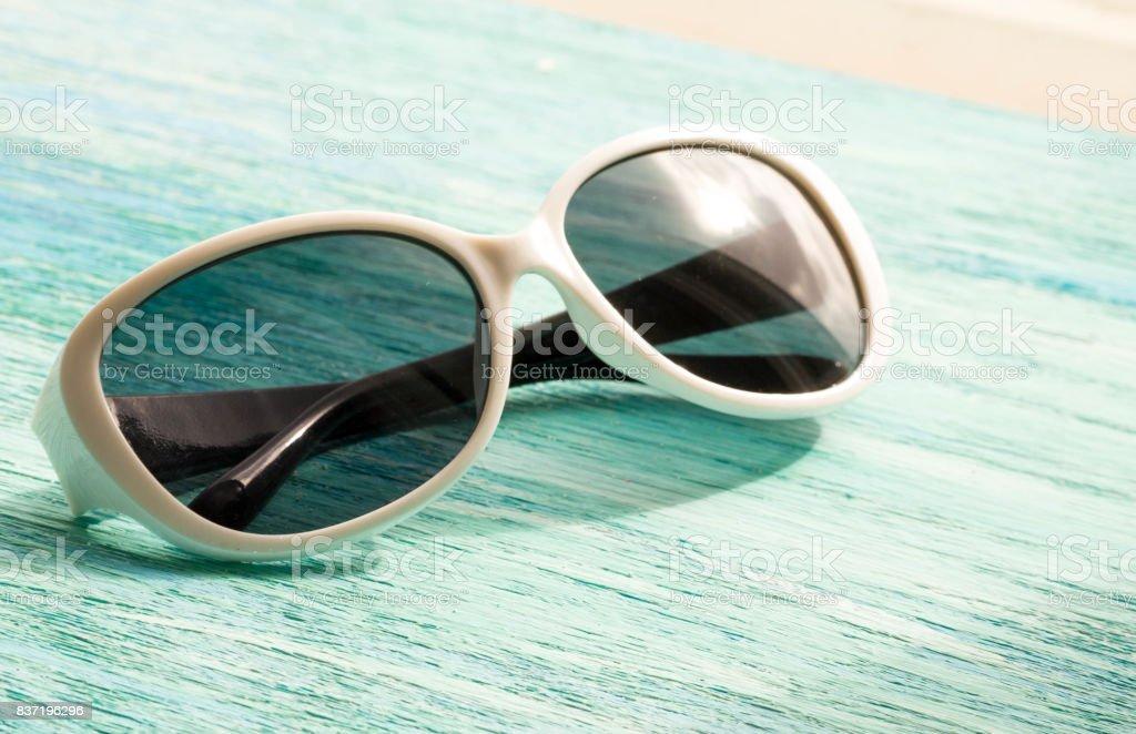Elegantes gafas de sol blanco sobre el fondo de madera de cerca. verano horizontal - foto de stock
