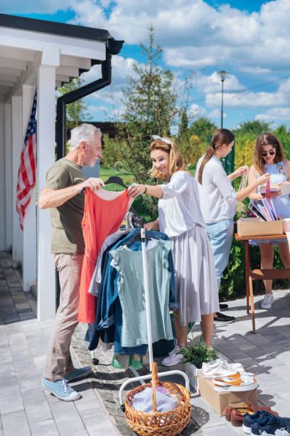 stilvolle frau trägt baggy sommerkleid blick auf neues rotes kleid am yard sale - hofkleider stock-fotos und bilder