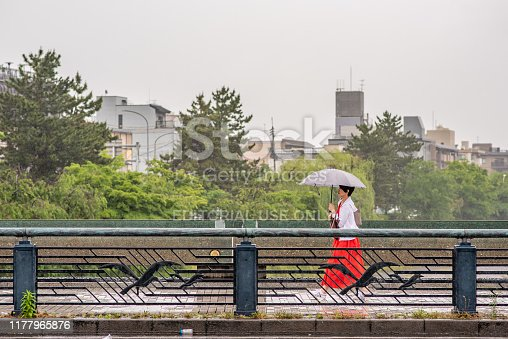 Kyoto, Japan - May 28, 2019: A stylish woman crosses the Shijo bridge on a rainy day downtown Kyoto. More than one million people live in Kyoto.
