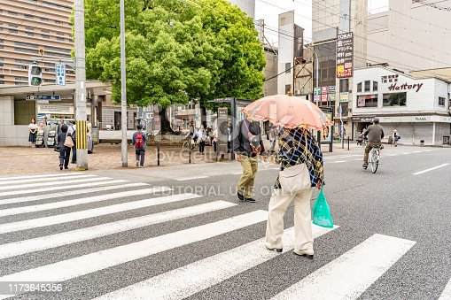 Kyoto, Japan - May 29, 2019: A stylish woman crosses the street carrying a parasol downtown Kyoto, in the business district, on a busy day. More than one million people live in Kyoto.