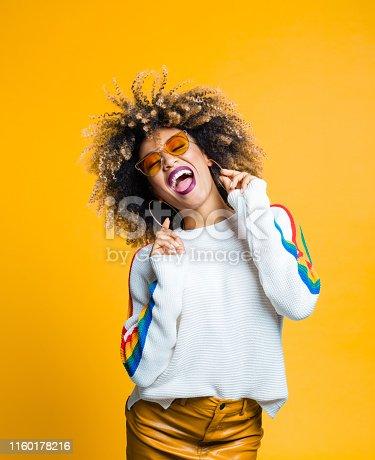 Portrait of stylish afro young woman enjoying against yellow background