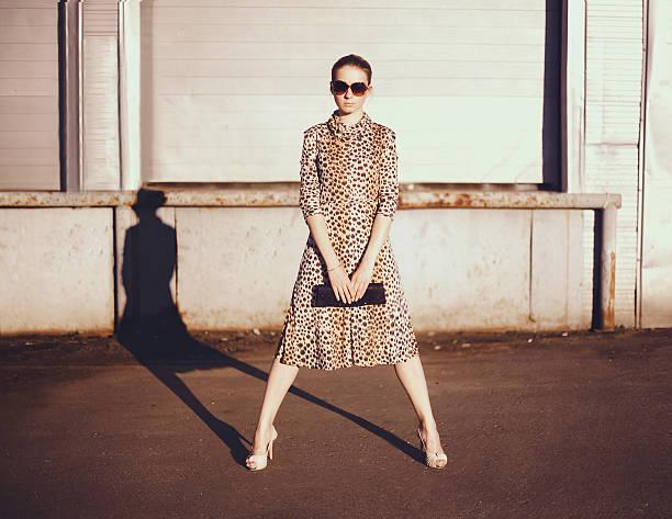 elegante frau in einem leopard kleid, brille und tasche - anzieh nacht stock-fotos und bilder