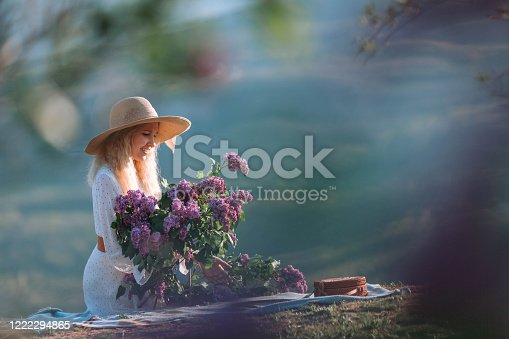 Stylish woman in a straw hat posing on lilac flowers on a background of mountains. Calm portrait of a beautiful girl standing with a bouquet of lilacs in the spring garden.