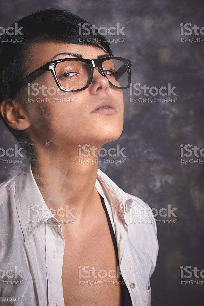 stylish woman in glasses smoking and blowing smoke, grey background stock photo
