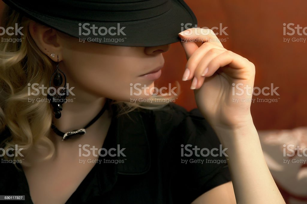 Stylish woman in hat hiding her face stock photo