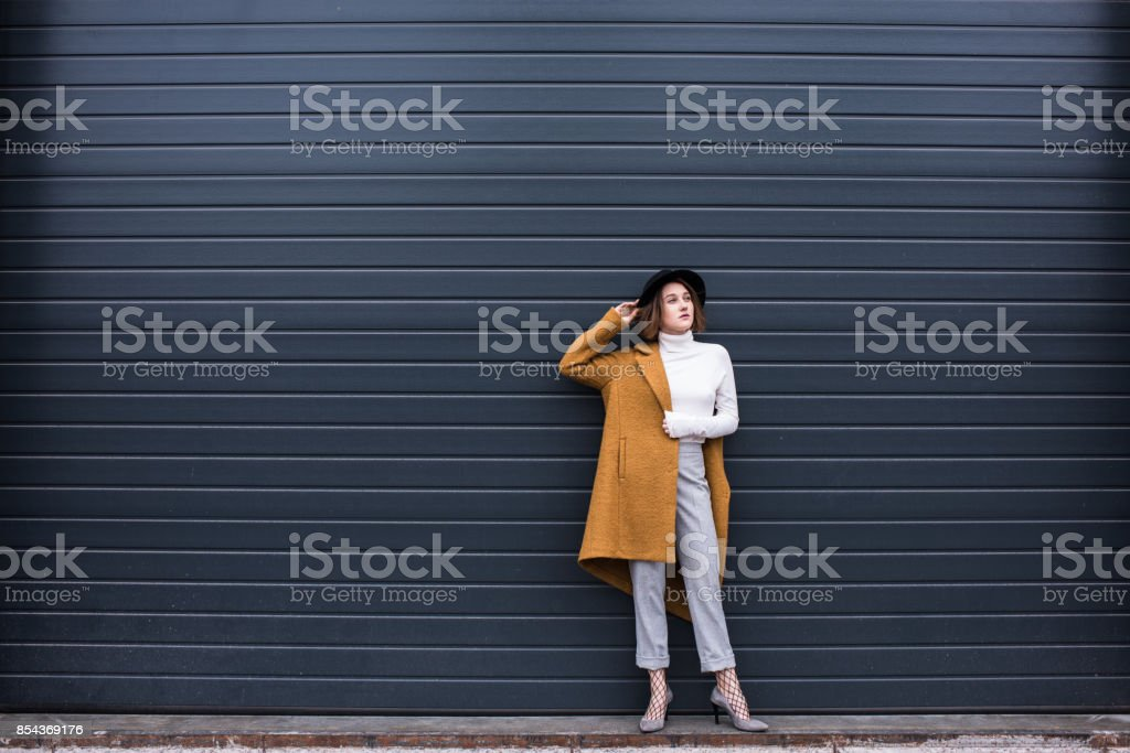 stylish woman in jacket and black hat stock photo