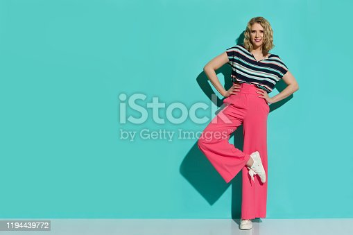 Stylish young woman in pink wide legs trousers, sneakers and striped blouse is posing on one leg. Full length studio shot on turquoise background.