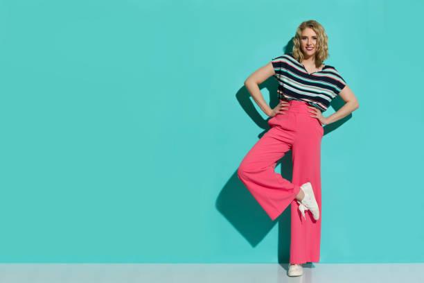 a mulher à moda em calças largas cor-de-rosa dos pés, nas sapatilhas e na blusa listrada está levantando em um pé - calça comprida - fotografias e filmes do acervo