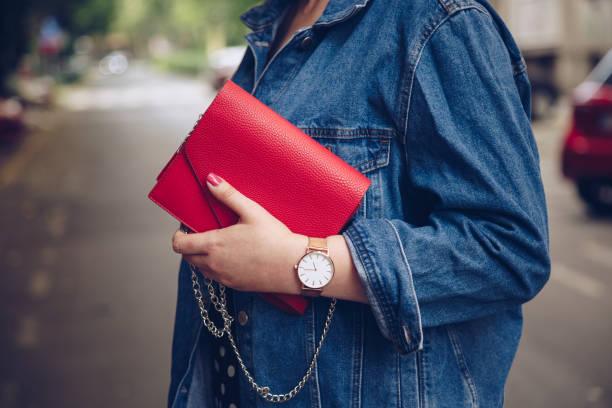 stilvolle frau polka dot culottes und jeansjacke hält eine rote handtasche und tragen eine rose gold armbanduhr - vogue muster stock-fotos und bilder