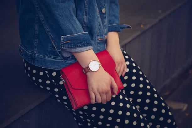 stilvolle frau polka dot culottes und jeansjacke hält eine rote handtasche und eine rose gold armbanduhr zu tragen. - vogue muster stock-fotos und bilder
