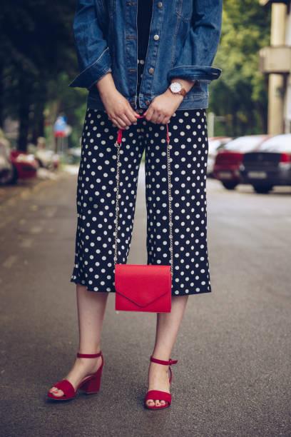 stilvolle frau polka dot culottes und roten high heel schuhe hält eine rote handtasche - vogue muster stock-fotos und bilder