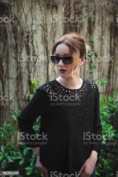 Foto de Elegante Mulher De Óculos Escuros E Camisa Preta Elegante e mais fotos de stock de Adulto