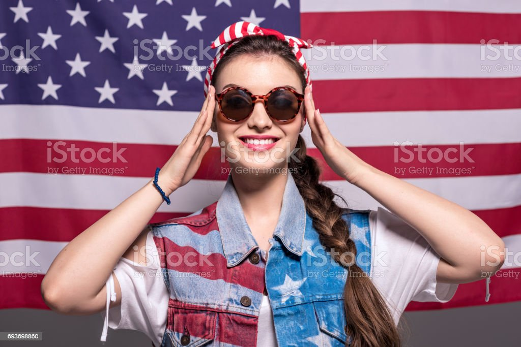 stylish woman in sunglasses with american flag behind stock photo
