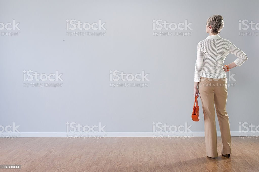 Stylish Woman Looking At Blank Wall stock photo