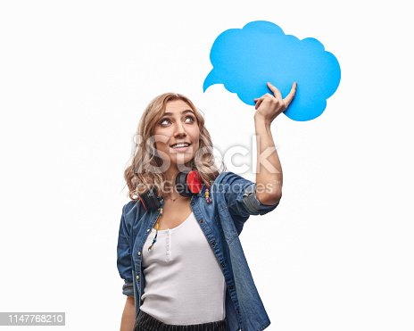 Attractive female in trendy outfit smiling and looking at blank blue speech bubble while standing against white background