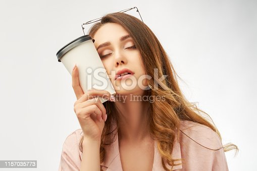 A stylish woman office worker holds a Cup of coffee at her head and closes her eyes and falls asleep. The concept of fatigue and lack of sleep, stress and drowsiness.