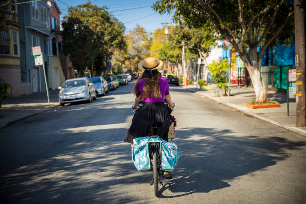 Stylish Woman Riding Heavily Loaded Bicycle Through San Francisco Street stock photo