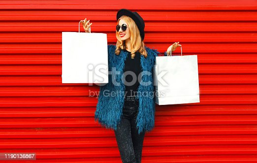Stylish woman showing and looking at two same shopping bags wearing blue faux fur coat, round hat and sunglasses over red wall background