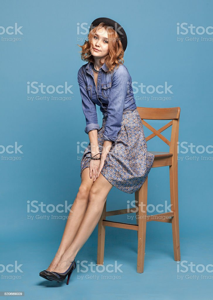 stylish woman sitting on a chair on a blue background stock photo