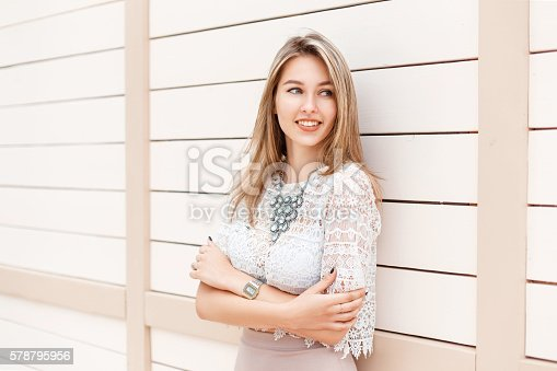 578791454 istock photo Stylish woman smiling in lace blouse and dress near wall. 578795956