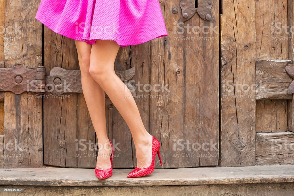 Stylish woman standing in front of old wooden doors stock photo