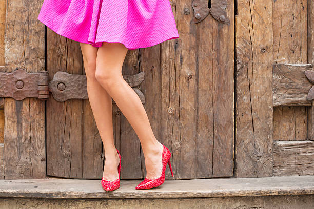 stilvolle frau steht im vor alten hölzernen türen - damen rock pink stock-fotos und bilder