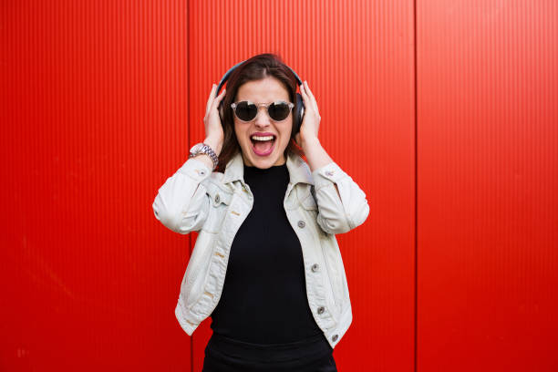 Stylish woman standing near red wall stock photo