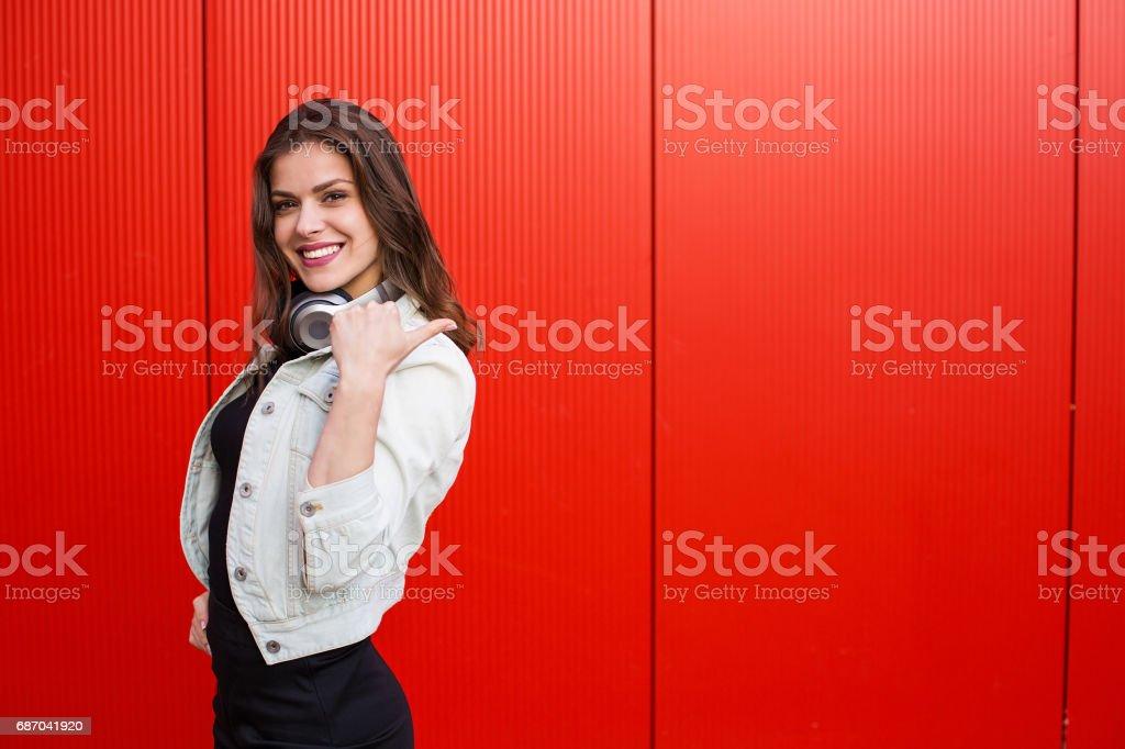 Stylish woman standing near red wall Lizenzfreies stock-foto