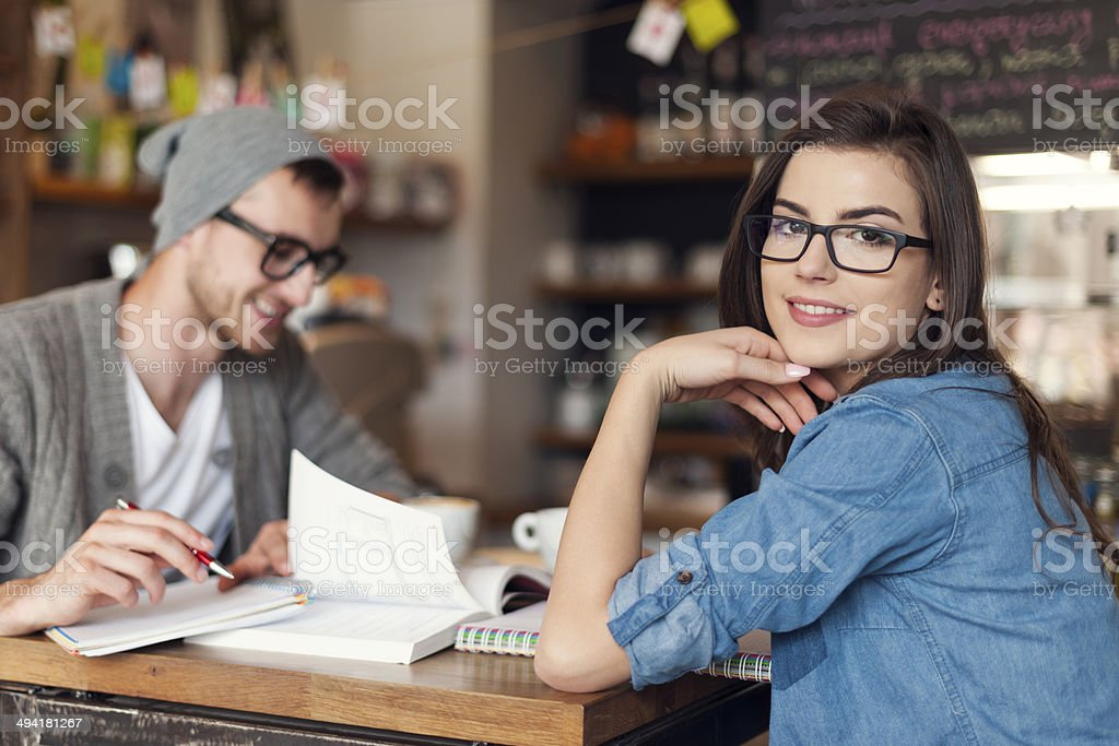 Stylish woman studying with her friend at cafe stock photo