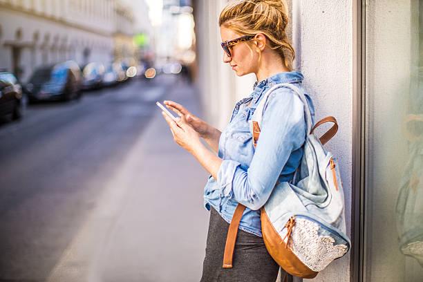 stilvolle frau mit einem smartphone im freien - damenrucksack stock-fotos und bilder