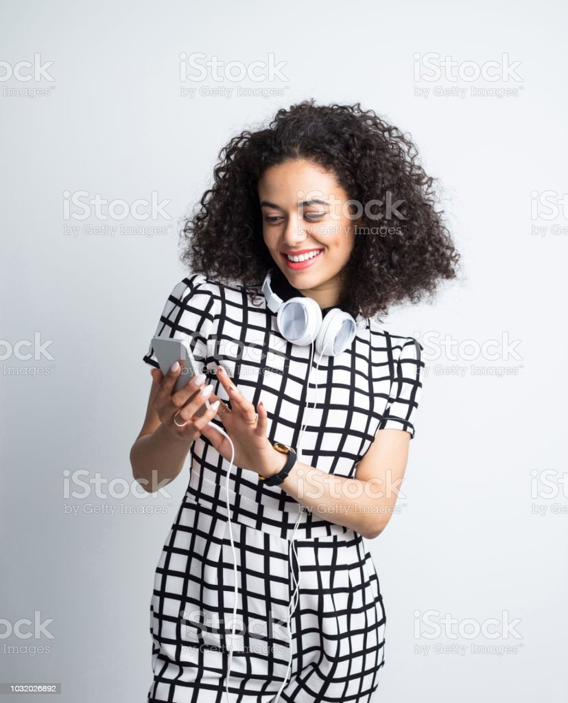 Stylish woman using smart phone in studio Pretty young woman with headphones using mobile phone on gray background. Stylish woman using smart phone in studio. 20-24 Years Stock Photo