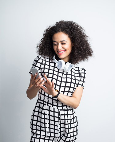 Stylish Woman Using Smart Phone In Studio Stock Photo - Download Image Now