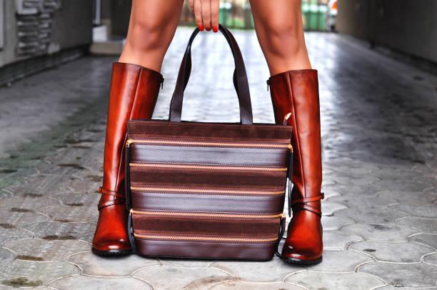 stilvolle frau zu fuß in stadtstraße, trägt braune lederstiefel und hält braunem leder und wildledertasche. herbst, winter-outfit - leder handtaschen damen stock-fotos und bilder