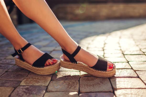 검은 여름 신발 짚 단독와 야외에서 착용 하는 세련 된 여자. 편안한 샌들입니다. 뷰티 패션입니다. - 샌들 뉴스 사진 이미지