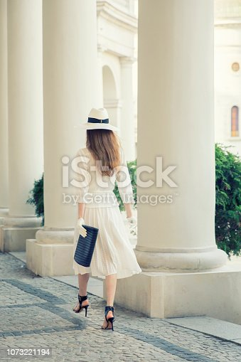 Elegant woman walking around city center. Wearing matching gloves, hat and dress