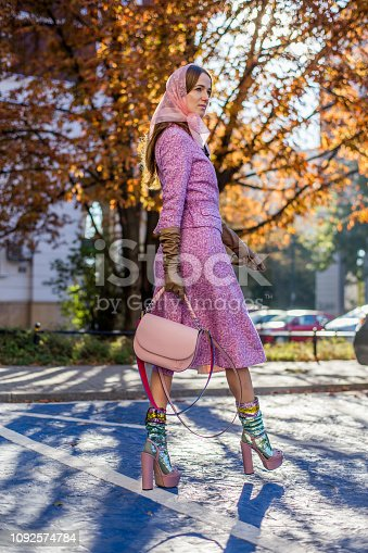 Elegant woman walking around public park. Wearing fashionable outfit