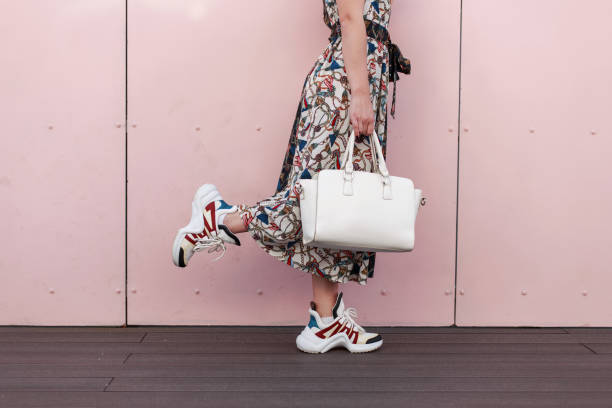 stilvolle frau mit einer weißen tasche in ein vintage-kleid mit modischen sneakers posiert in der nähe der rosa wand. close-up. das konzept des einkaufens - vogue muster stock-fotos und bilder