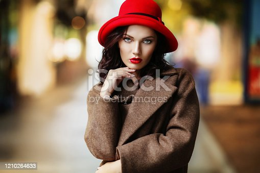 518885222istockphoto Stylish woman with bright evening make-up in red gloves and a red evening hat in the city in an autumn coat 1210264633